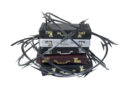 Sharp razor wired used as a barrier around a stack of briefcases - path included