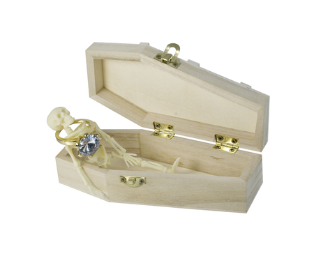 Skeleton wearing Diamond Engagement Ring lying in a Coffin - path included Stock Photo