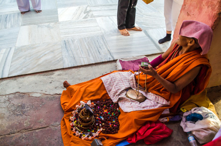 BODHIGAYA, INDIA - MAY 13, 2014: An Unknow Tibetan Buddhist nun give her tibet stone to many people  around Mahabodhigaya temple where buddha got enlightment on 13 May 2014