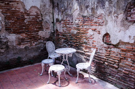 Garden furniture set with old brick wall photo