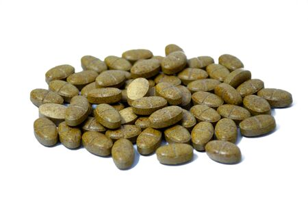 Side view of multivitamin brown tablets on white background