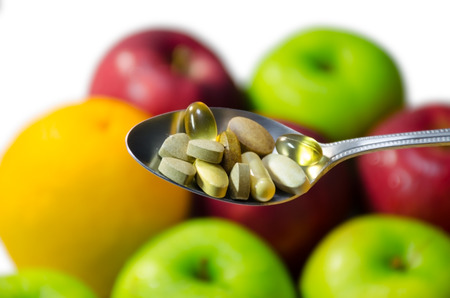 multivitamin: Assorted vitamins and nutritional supplements in serving spoon. on blur colorful fruits background