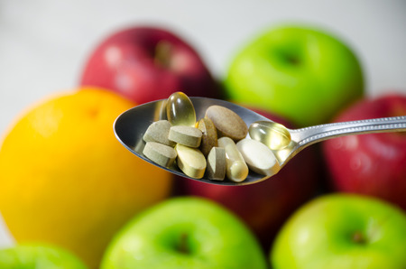 Assorted vitamins and nutritional supplements in serving spoon. on blur colorful fruits background photo