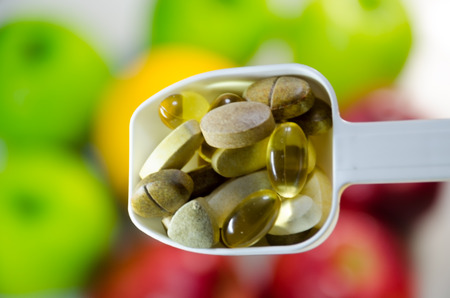 multivitamin: Assorted vitamins and nutritional supplements in white  serving spoon on blur colorful fruits background
