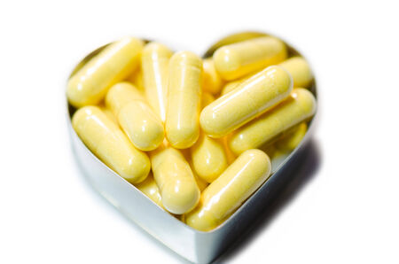 yellow food supplemnet CoQ10 (Co-enzyme Q10) capsules in heart shape box closeup on white background isolated