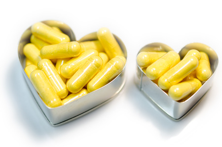 yellow food supplemnet CoQ10 (Co-enzyme Q10) capsules in two heart shape boxes closeup on white background isolated