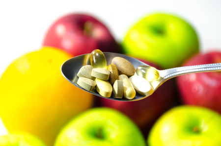 Assorted vitamins and nutritional supplements in serving spoon with sunlight on blur colorful fruits background