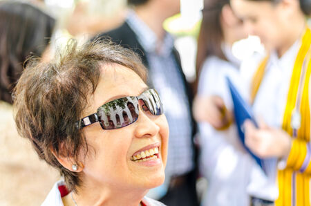 Potrait of old Asian Thai woman wearing sunglasses smile with happiness in graduation celebration  of her grandchild