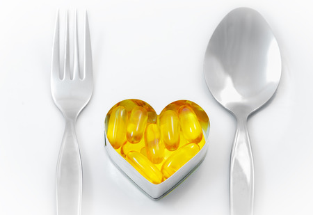 Fish Oil On Heart as Main menu between fork and spoon isolated on white background photo