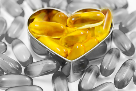 Fish oil pills on heart shape box among piles of fish oil pills black and white isolated on white background split tone