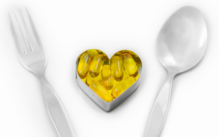 Fish Oil On Heart as Main menu between fork and spoon isolated on white background, You can add text or anything in the space photo