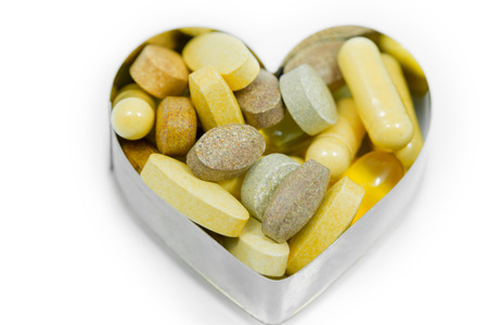 Multi food supplement pills in heart isolated on white background with many kind of tablets and capsules such as yellow capsules,multi vitamin tablets, and fish oil etc. photo