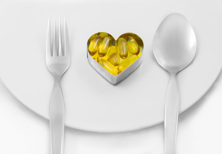 Fish Oil On Heart as Main menu between fork and spoon ion white dish solated on white background photo