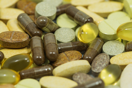 Drugs and food supplements pills and capsules macro background photo