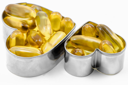 Two fish oil pills in heart shape box isolated on white background photo