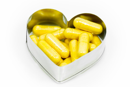 Yellow capsules in heart shape box isolated on white background