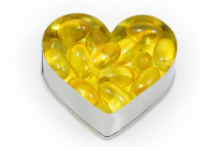 Fish oil on heart shape box isolated on white background photo