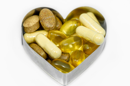 Multi food supplement pills in heart isolated on white background photo