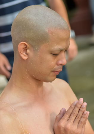 ordinate: Bangkok, Thailand - October 25, 2014 :An Thai male sit for  Buddhism ordain ritual  have a shower to clean body at Wat Thapra Temple in Thonburi Area  Bangkok, Thailand