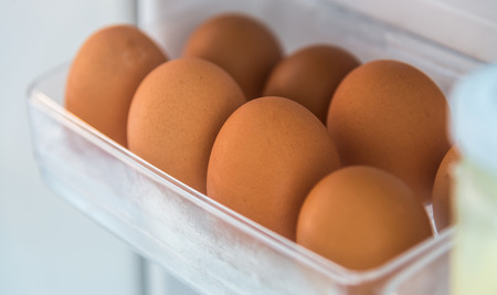 Raw Eggs in refrigerator shelf closeup Stock Photo