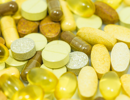 Mix of Drugs and food supplements pills and capsules macro background photo