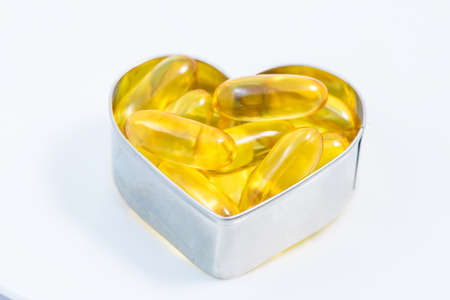 Fish Oil pills on heart   closeup isolated on white background photo