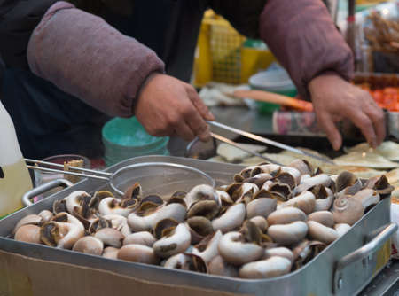 animal body part: Merchant cooking food from boiled Pond Snail (or Marsh snail)  as Korean traditional street food closeup