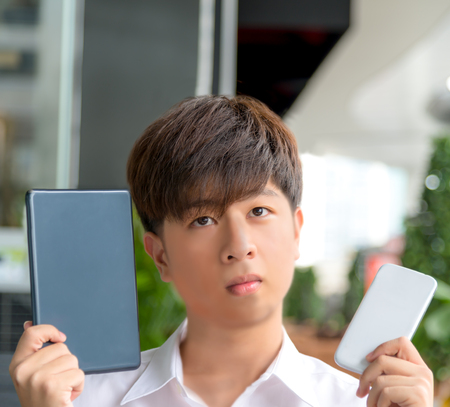 HESITATE: Asian male decide and hesitate to use  smart device tablet or smartphone and see above Stock Photo