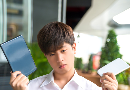 decide: Asian male decide and hesitate to use  smart device which one tablet or smartphone
