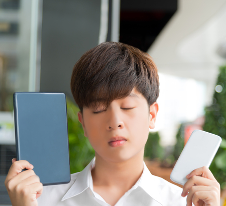 HESITATE: Asian male decide and hesitate to use  smart device tablet or smartphone and close his eyes
