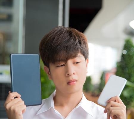 decide: Asian male decide and hesitate to use  smart device tablet or smartphone and see above Stock Photo