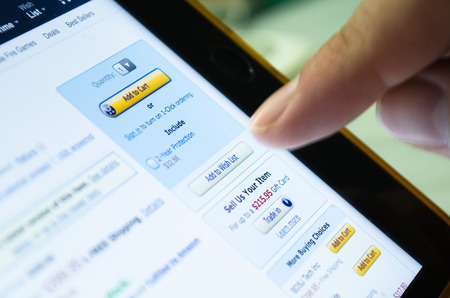 wish  list: Bangkok, Thailand - June 17, 2015  : Unidentified human finger touch on screen of tablet device on Add to Wish List button in Amazon ,largest famous online shopping website, to buy some product Editorial