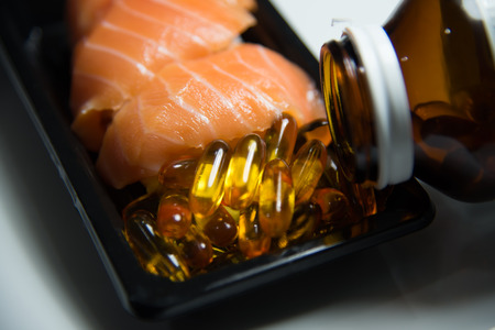 packs of pills: Sushi salmon served with fish oil  pills poured from bottle isolated on white background