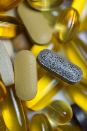 else: Food supplements pills or capsules drugs macro consist of fishoil , ,multivitamin,fruit and vegetable extract tablet ,lutein and else vertical macro Stock Photo