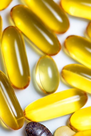 food supplement: Fish oil and food supplement  pills macro vertical isolated on white background Stock Photo