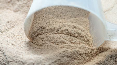 deluxe: Isolate protein powder chocolate deluxe flavour with scoop macro closeup
