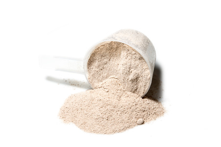 Scoop of Isolate protein powder chocolate deluxe flavour  poured isolated on white background Stock Photo