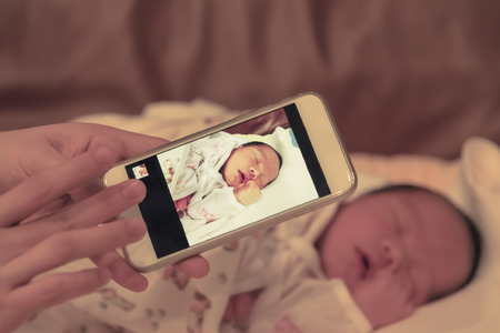 infant hand: Asian mother take a photo of her baby female son with smart phone focused on the device
