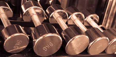 Dumbells in gym  copper sepia vintage tone