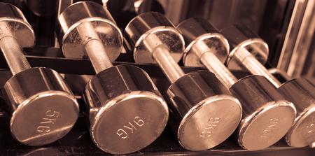 Dumbells in gym  copper sepia vintage tone