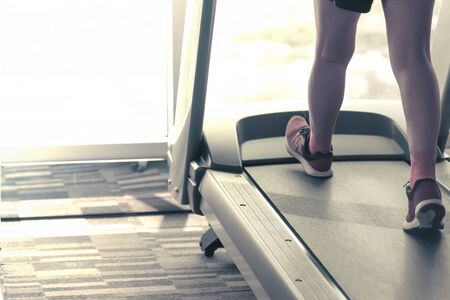shining light: Unknown woman wear pink running shoes workout by running using  thread mill in fitness with shining light