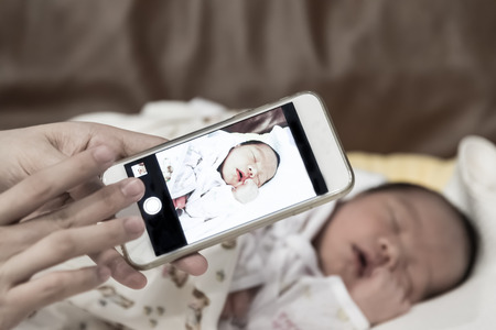 smart girl: Asian mother take a photo of her baby female son with smart phone focused on the device