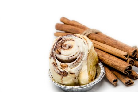 cinnamon swirl: Mini cinnamon roll with roped cinnamon stick isolated on white background focused on the roll