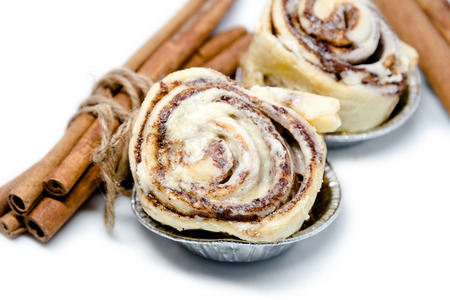cinnamon swirl: Mini cinnamon rolls with roped cinnamon stick isolated on white background focused on the front roll Stock Photo