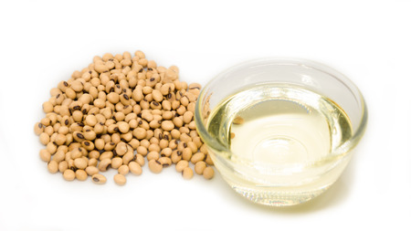 Soybean oil on glass bowl and pile of soybeans isolated on white background