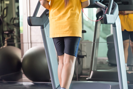 yellow shirt: Unknown woman on yellow shirt running in gym using treadmill