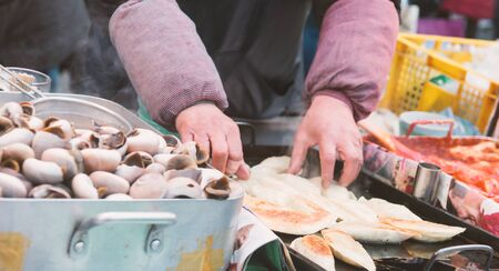 bodypart: Unidentified merchant cooking food from boiled Pond Snail or Marsh snail  as Korean traditional street food closeup