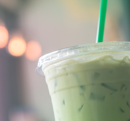 Plastic cup of Iced matcha  with green straw in pastel green