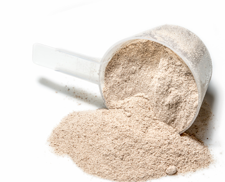 white powder: Scoop of Isolate protein powder chocolate deluxe flavour  poured isolated on white background Stock Photo