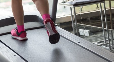 Unknown woman with pink shoes running with treadmil in gym closeup